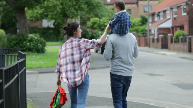 I Love Mum and Dad! A family of three are on a walk outdoors whilst the father is giving his mixed-race son a piggyback. prop stock videos & royalty-free footage