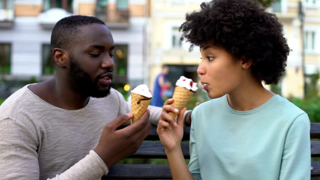 vídeos de stock e filmes b-roll de love partners sharing ice-cream during summer date in city park, fun together - namorado