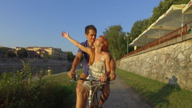 Love ride Young man riding a bicycle and his girlfriend on it. They are passing through the quayside; woman is raising her arms and enjoying. redhead stock videos & royalty-free footage