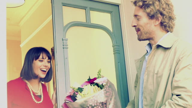 Love, romance and flowers. Vintage. A loving man giving a bunch of flowers to a smiling beautiful woman at her front door. Hand held vintage effect. giving stock videos & royalty-free footage