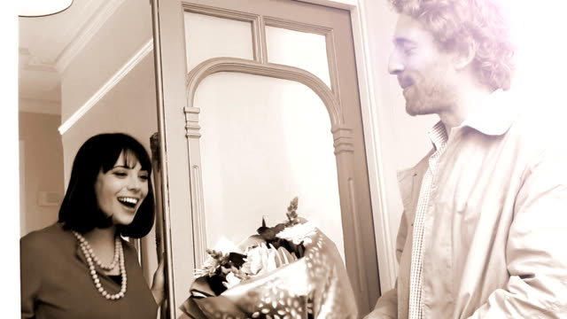 Love, romance and flowers.Sepia. A loving man giving a bunch of flowers to a smiling beautiful woman at her front door. Sepia tone with a 1960s feel, hand held. sepia toned stock videos & royalty-free footage