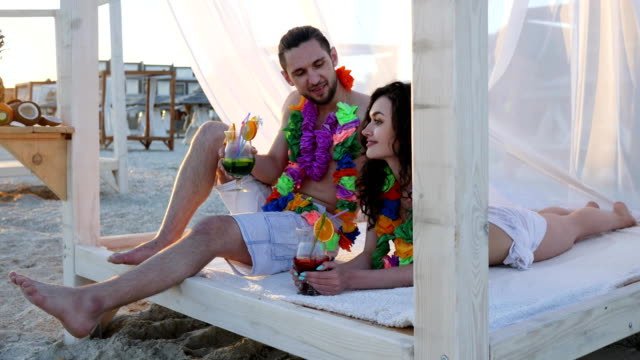 love romantic couple an exotic vacation, summer holiday for young people, Girl dresses Hawaiian lei on neck of guy in backlight video