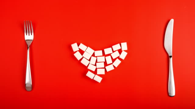 love sugar. heart from sugar cubes on red background video