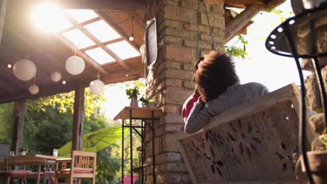 I love this kind of morning with you! Young family with one child have a good time on the porch swing porch stock videos & royalty-free footage