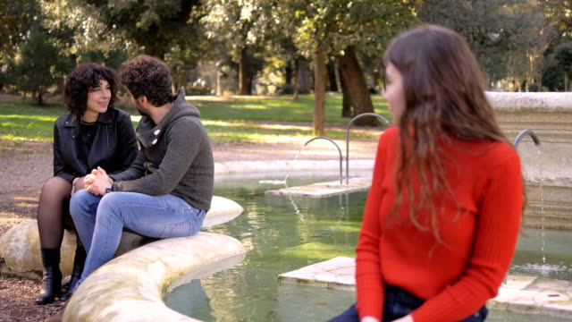 love triangle. young sad woman looking at ex boyfriend kissing other woman - rivalità video stock e b–roll