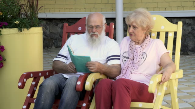 Loved husband reads a book a beautiful wife, old people relax in rocking chairs video
