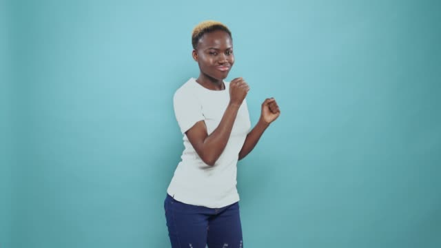 lovely african lady actively moving to music in studio - maglietta bianca video stock e b–roll