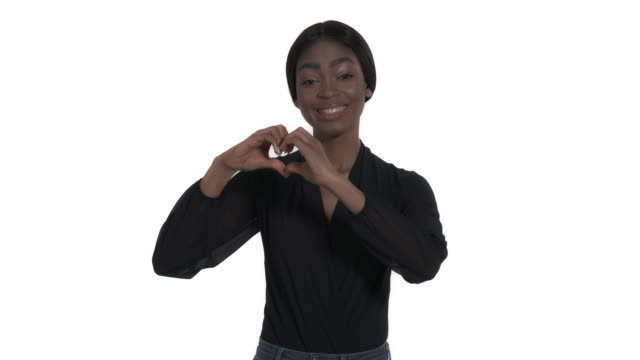 Lovely Afro woman with charming smile holding hands in heart shape showing her love and sympathy. Body language concept. Isolated, on white background