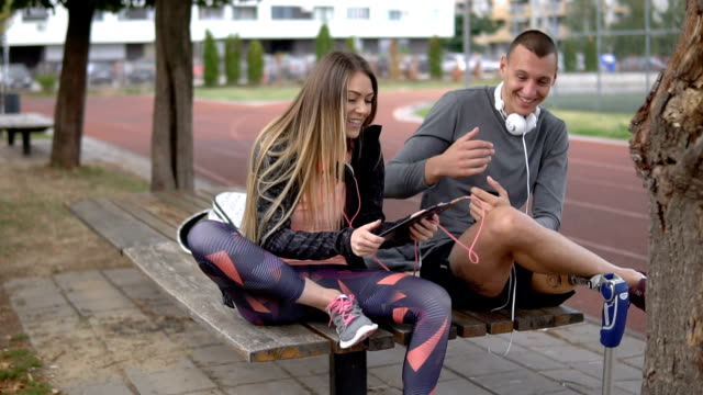 Lovely athletic couple laughing while listening to music Young and handsome athletic amputee and his girlfriend, taking a break from running, listening to music next to a running track. artificial limb stock videos & royalty-free footage