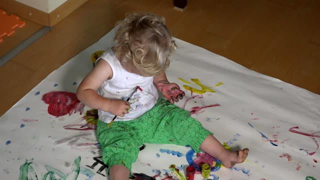 schöne mädchen mit bunten pinsel malen auf sich selbst kleidung - schmutzfleck stock-videos und b-roll-filmmaterial