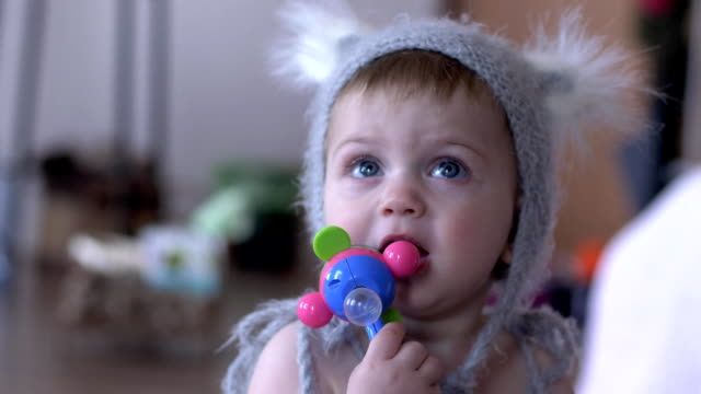 lovely baby gnawing toy in hands on unfocused background - ciuccio video stock e b–roll