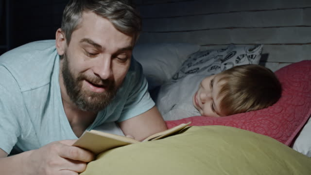 lovely boy listening to dad reading fairytale - padre single video stock e b–roll