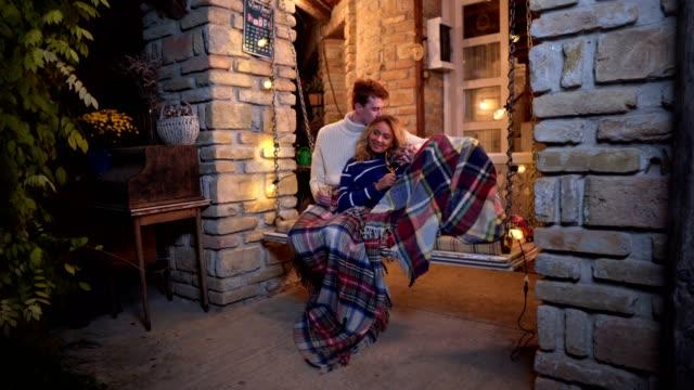 lovely boyfriend kissing his girlfriend on a porch swing - portico video stock e b–roll