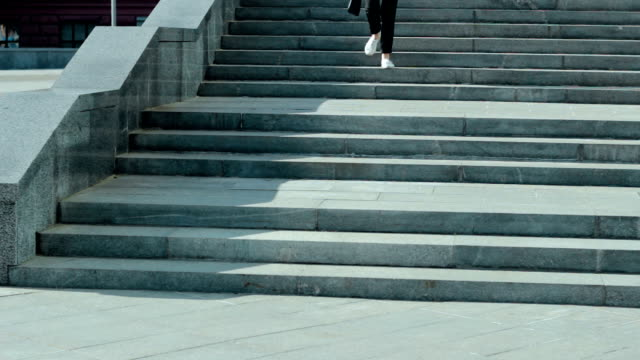 lovely business woman goes down the stairs video