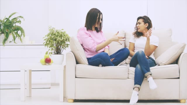 lovely kaukasiska och afro-amerikanska flickor sitter på soffan, pratar vänligt och känslomässigt, leende. - kvinna ventilationssystem bildbanksvideor och videomaterial från bakom kulisserna