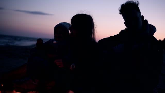 Schöne, kaukasische Familie von drei sitzen neben dem Lagerfeuer - Vater spielt Gitarre, junge langhaarige Frau füttert ihr süßes Baby mit gerösteten Marshmallow und wärmen ihre Hände mit Feuer – Video