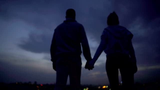 Lovely couple holding hands, romantic secret place for dating, relationship video