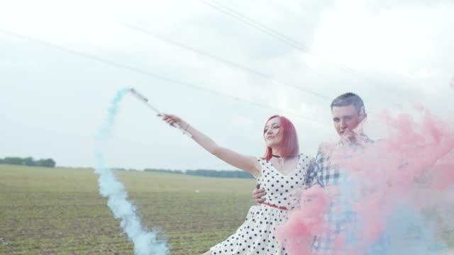Lovely couple making colored smoke heart outdoors