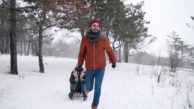 lovely couple sledding on snowy winter day. man pull sled with girlfriend on snowfall. woman have fun and sledge outdoors with boyfriend. people sleigh ride and enjoy christmas vacation. slow motion - slitta video stock e b–roll