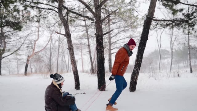 härligt par spann på snöig vinterdag. man pull släde med flickvän på snöfall. kvinnan har kul och släden utomhus med pojkvän. människor slädtur och njuta av julen semester. slow motion - snow kids bildbanksvideor och videomaterial från bakom kulisserna