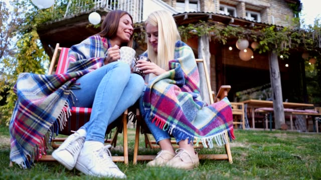 Lovely couple spending cozy moments with tea in lounge chairs outdoors