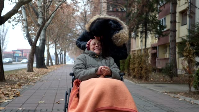 Lovely daughter kissing her mother in a wheelchair Senior woman in a wheelchair being pushed through the city by her daughter. sociology stock videos & royalty-free footage
