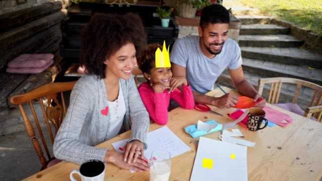 Lovely family having fun while doing a art project for school Lovely mixed race child doing homework with the help of her parents. royalty stock videos & royalty-free footage