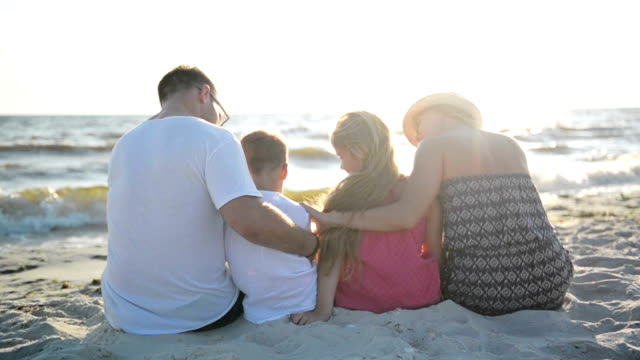 Lovely Family Hugging Sitting on the Sand near the Sea and Looking on the Sun and Waves video
