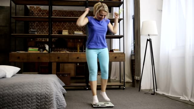 Lovely fit woman celebrating weight loss indoors Beautiful fit woman in casual outfit with measuring tape in hand standing on scale and celebrating weight loss in domestic interior. Excited girl gesturing happiness after achieving weight loss goal plus size model stock videos & royalty-free footage