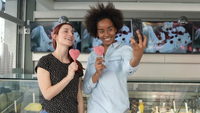 Lovely friends taking a selfie with her Popsicles at the ice cream shop