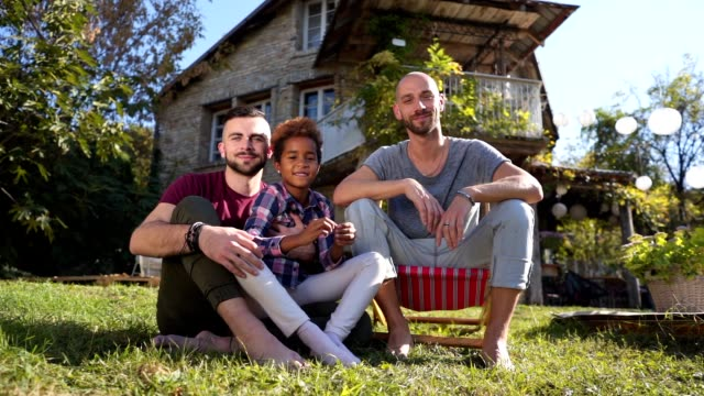 lovely gay family with a adopted mixed race daughter - coppia gay video stock e b–roll