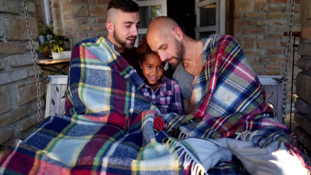 Lovely gay family wrapped in a blanket on a front porch