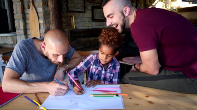 lovely gay parents making art with their adopted daughter - coppia gay video stock e b–roll