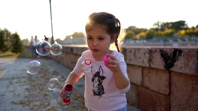 Lovely girl blowing bubbles out of soap