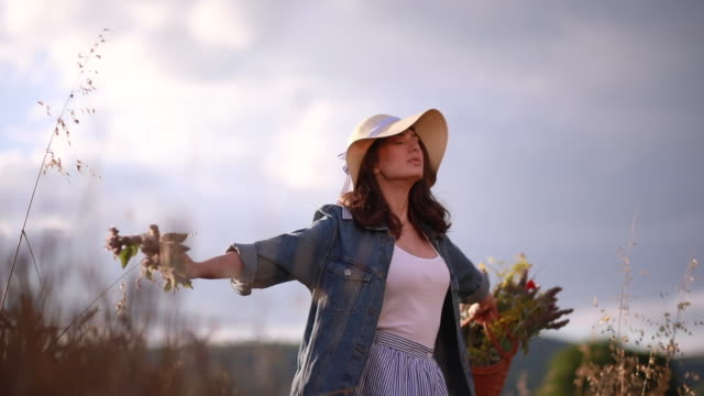 Lovely girl in denim jacket spinning on a golden field holding flowers Lovely and gorgeous hipster girl in denim jacket, with a basket full of flowers and a hat, traveling through a golden wheat field. 天の川 stock videos & royalty-free footage