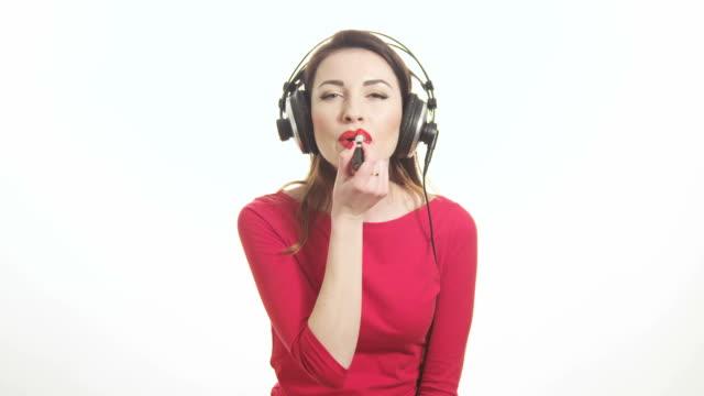 Schöne Mädchen hören die Musik im Kopfhörer red lipstick – Video