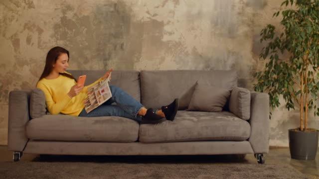 stockvideo's en b-roll-footage met mooi meisje lezen magazine en ontspannen op de sofa - woman home magazine