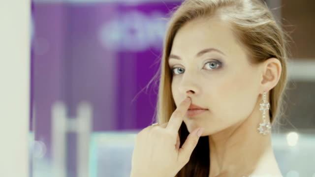 Lovely girl wears jewelry in the bathroom. video