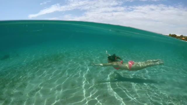 UNDERWATER: Lovely girl with long brown hair swimming underwater in ocean video