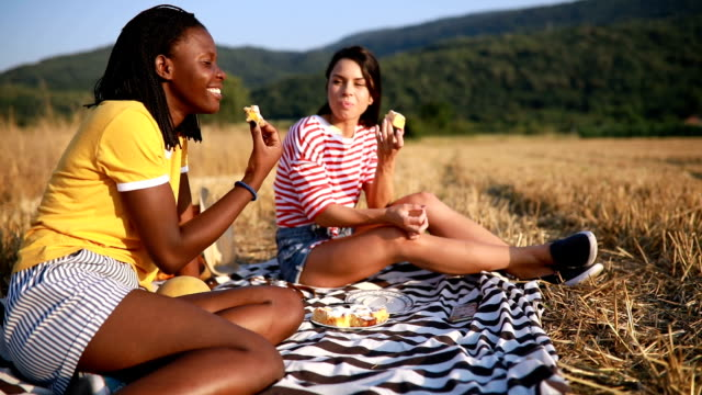 Lovely girls eating cake in nature on a picnic
