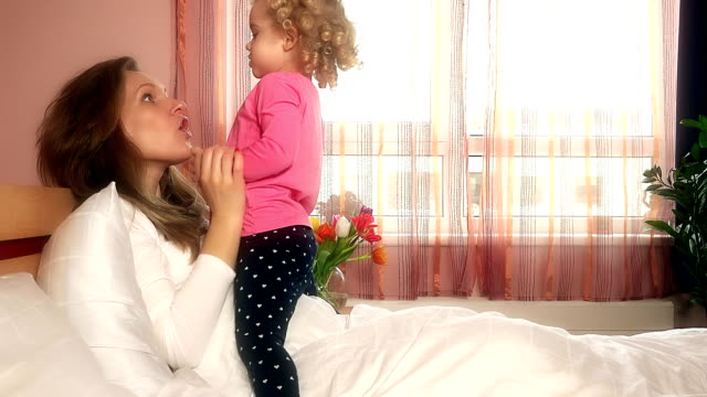 Lovely girls mother and little daughter show feelings in bedroom video