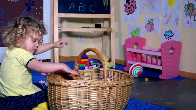 Lovely little girl child put all toys into wicker basket. Kid tidy clean up room video