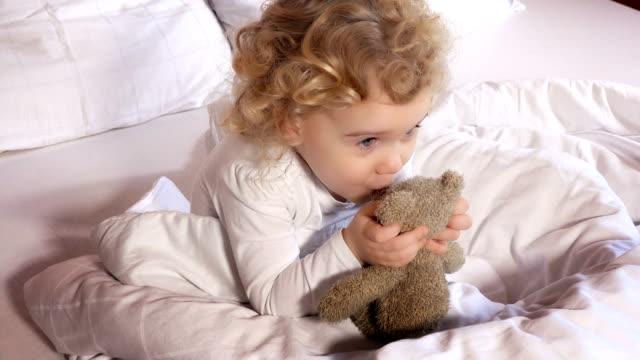 vídeos de stock e filmes b-roll de lovely little girl kiss her best friend loved teddy bear toy sit in white bed - teddy bear