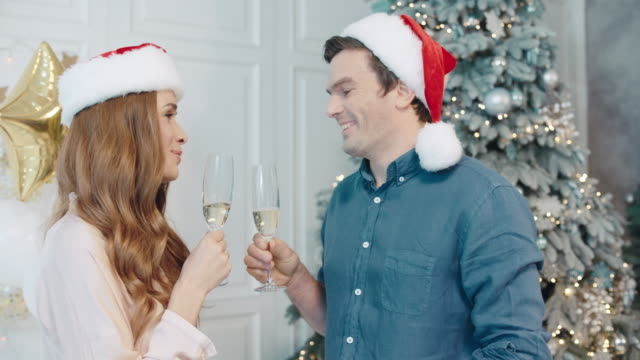 Lovely man and woman making wish on new year night at santa hats together.
