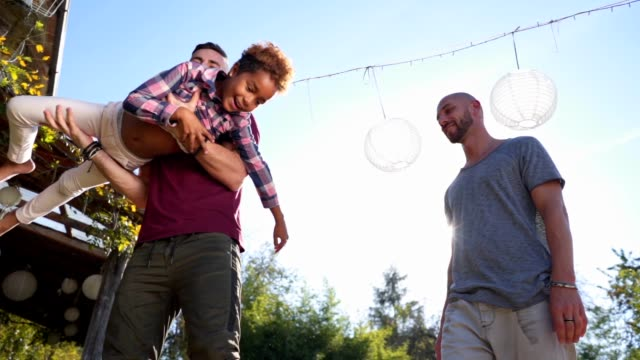 Lovely mixed race daughter having fun with her parents Beautiful and lovely gay homosexual couple enjoying their time spent together as a family with their beautiful adopted mixed race daughter. lgbtqi rights stock videos & royalty-free footage