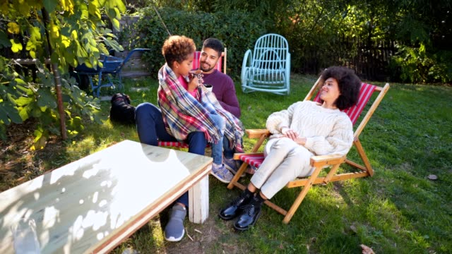 Lovely mixed race family spending their leisure time in a back yard