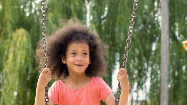 Lovely mixed-race girl with curly hair swinging with great enthusiasm, slow-mo video