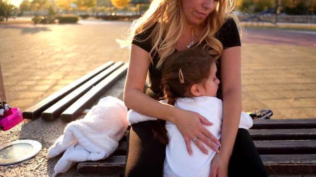 Lovely mother consoling her child while embracing her Beautiful toddler girl and her mother, sitting at a public park, consoling and hugging. comfort stock videos & royalty-free footage