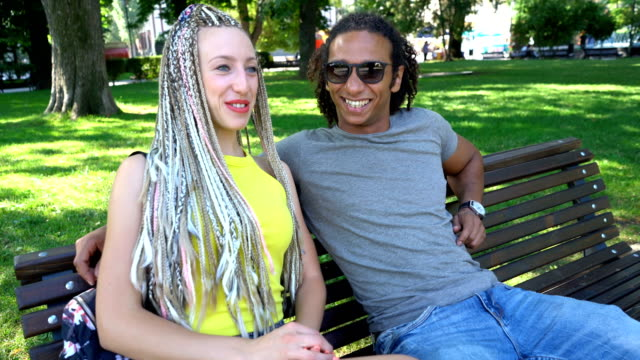 Lovely multiracial couple sitting on the park bench and talking. video