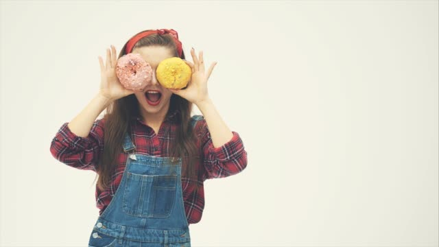 lovely pinup girl is hiding her eyes behind big pink and yellow doughnuts, posing, smiling. - donna si nasconde video stock e b–roll